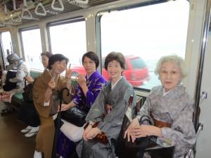 江ノ電車中 雨に煙る江ノ島の海を背景に